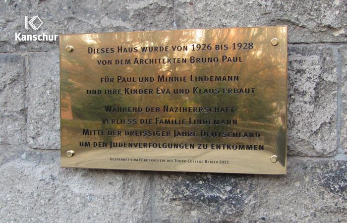 Gedenktafel aus polierten Messing mit Gravur an Natursteinwand mit Abstandhalter befestigt